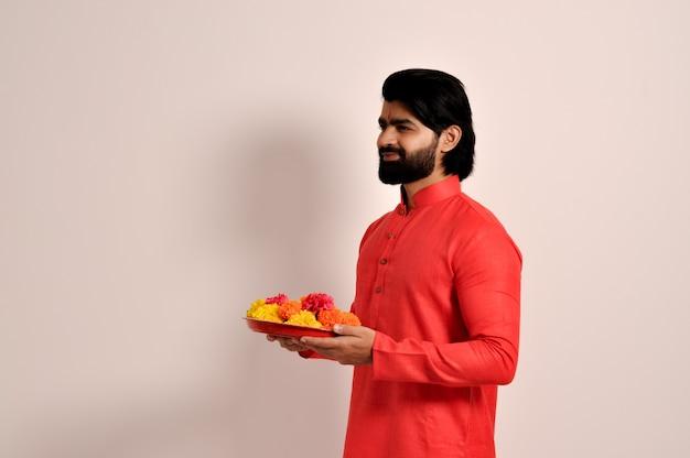 금잔화 꽃 화환 접시 측면 보기를 들고 오렌지 kurta를 입고 젊은 인도 잘생긴 남자