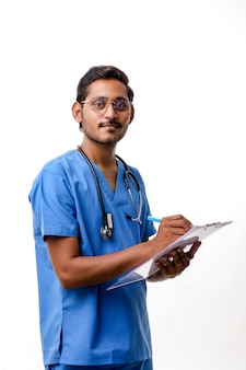 흰색 배경 위에 격리된 메모장에서 청진기를 들고 제복을 입은 젊은 인도 남성 의사.