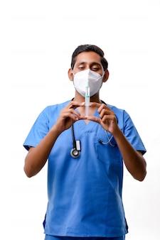 白い背景の上の手にロードされた注射器を保持している若いインド人男性医師。