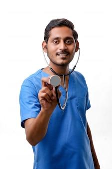 흰색 배경에 청진기를 손에 들고 젊은 인도 남성 의사.