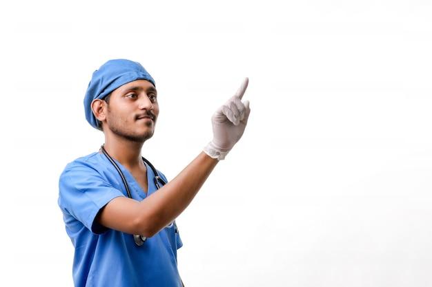 白い背景の上に指で指している若いインドの男性医師。