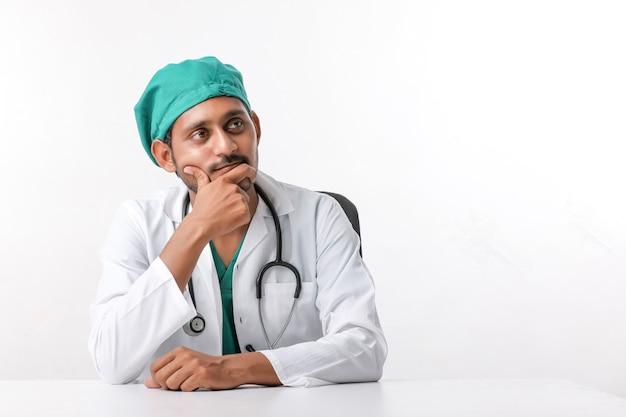 Молодой индийский мужчина-врач показывает выражение в клинике.