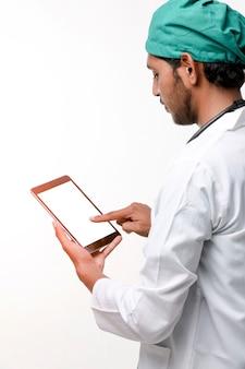 Молодой индийский мужчина-врач с помощью смартфона в клинике.