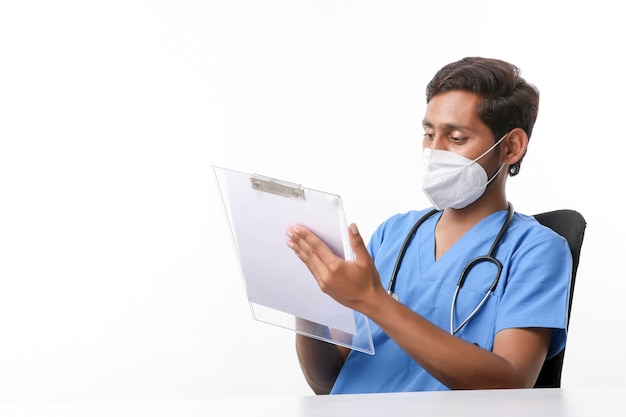 Young indian male doctor writing on notepad at clinic.