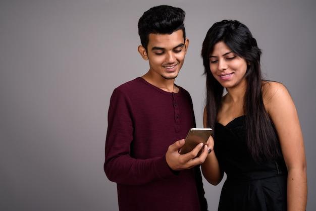 Молодой индийский мужчина и молодая индийская женщина вместе на серой стене
