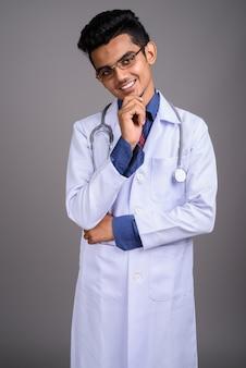 Молодой индийский мужчина доктор против серой стены