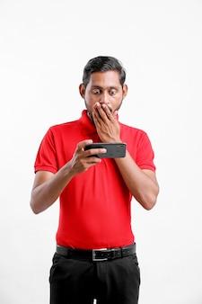 スマートフォンで見た後に衝撃的な表情を与える若いインド人