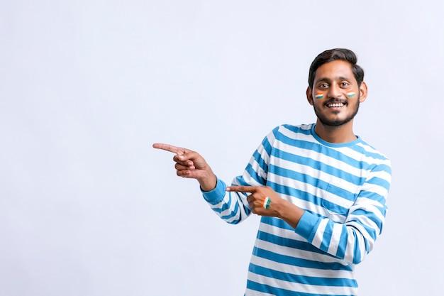 衝撃的な表情を与え、手で方向を示す若いインド人