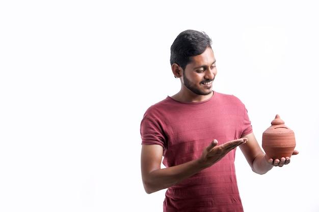흰색 배경 위에 점토 돼지 저금통을 손에 들고 젊은 인도 남자.