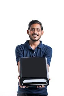 白い背景に電気ストーブを手に持っている若いインド人。