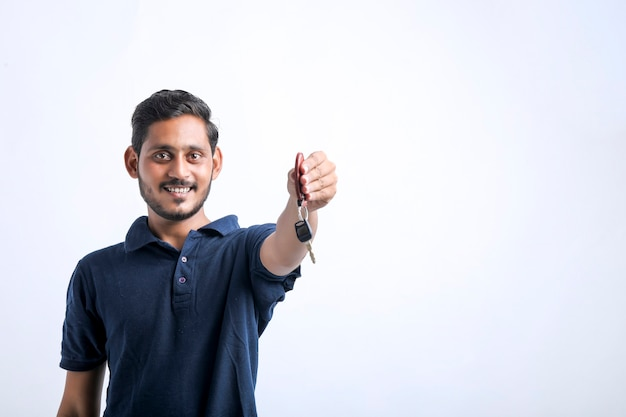 흰색 배경 위에 키를 손에 들고 젊은 인도 남자.