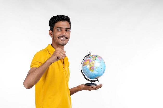 手のひら地球世界の地球を手に持っている若いインド人
