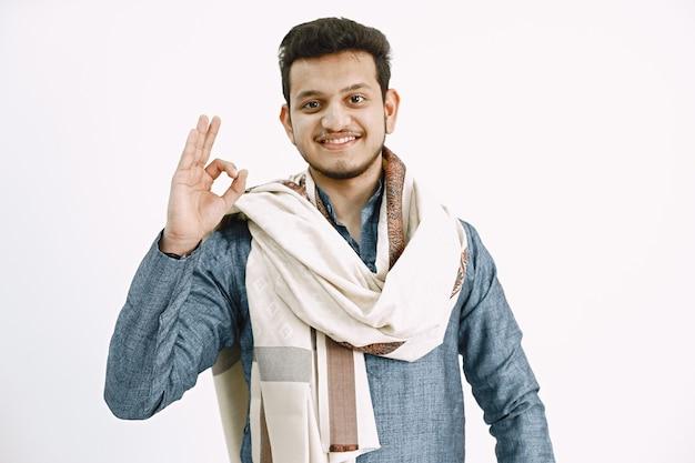 Okサインを示す伝統的な身に着けている若いインド人。白い壁。