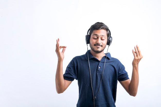 Young indian man listening music and showing expression over white background.