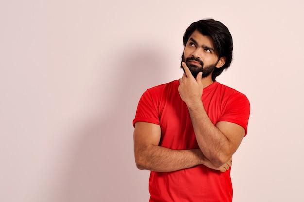 Молодой индийский мужчина смотрит вверх задумчиво делая выбор или размышляя обдумывая