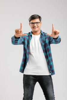 Молодой индийский мужчина делает кадр с рукой над белым