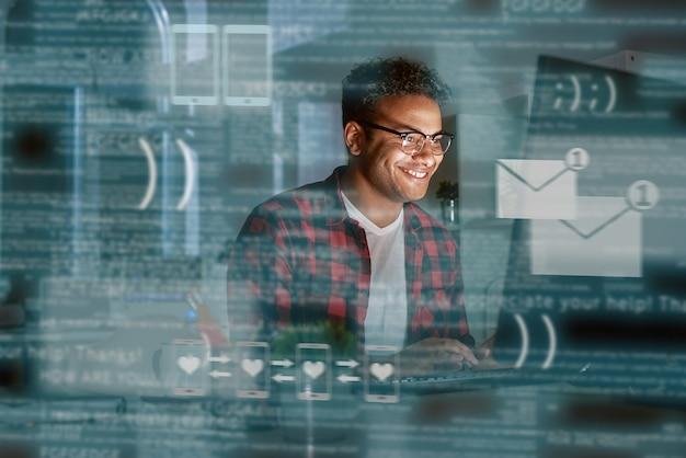 若いインド人男性が人気の出会い系アプリからメッセージを受け取りました。彼は眼鏡をかけて笑っている