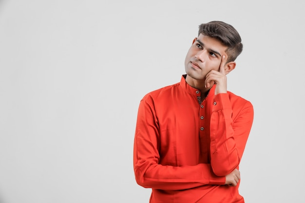 Young indian man in red shirt and thinking big idea on white