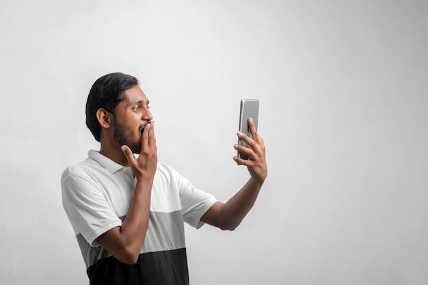 スマートフォンで表情を衝撃的な若いインド人