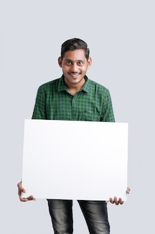Young indian man showing blank sing board over white background