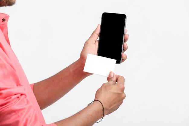 Молодой индийский мужчина показывает карту и смартфон на белой стене