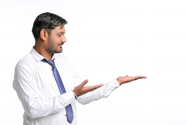 흰색 배경에 식을 보여주는 젊은 인도 남자
