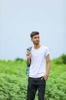자연 배경 위에 표현을 보여주는 젊은 인도 사람