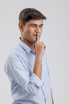 Young indian man showing finger on lips, or secret gesture hand sign