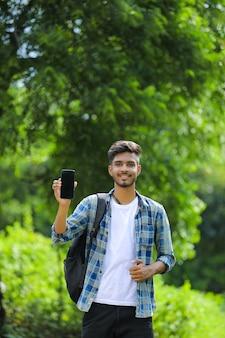 モバイル画面を表示している若いインド人