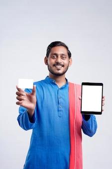 흰색 배경 위에 태블릿 및 카드를 보여주는 젊은 인도 남자.