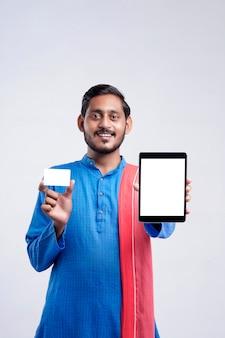 흰색 배경 위에 태블릿과 카드를 보여주는 젊은 인도 남자.