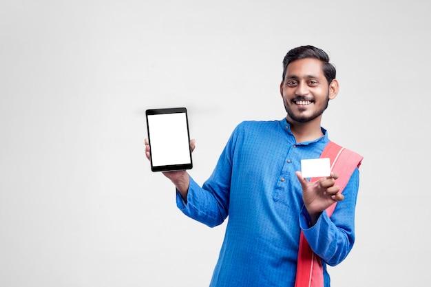 Молодой индийский человек показывает таблетку и карточку на белом фоне.