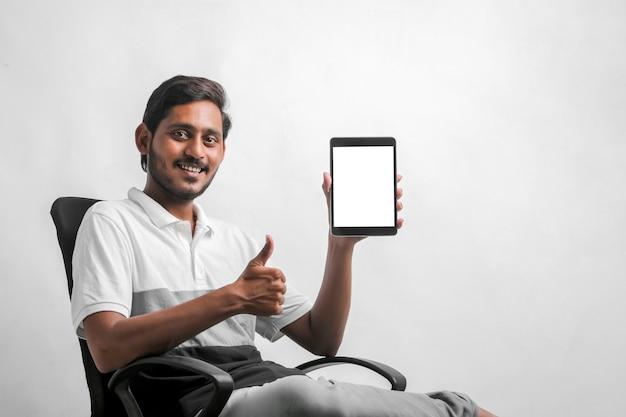 흰색 배경 위에 태블릿을 보여주는 젊은 인도 남자.