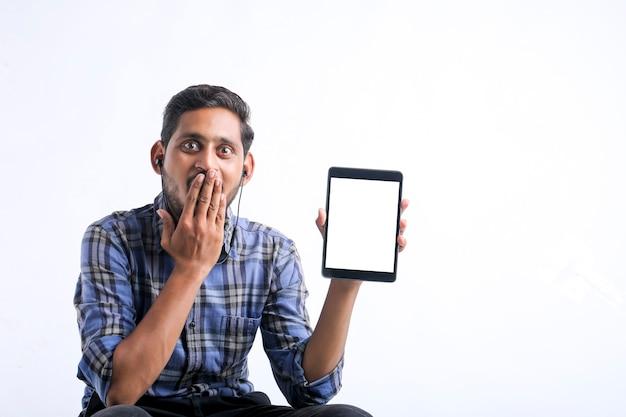 白い背景の上にタブレットを示す若いインド人。
