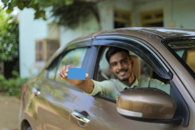 カードを示す彼の新しい車の中に座っている若いインド人