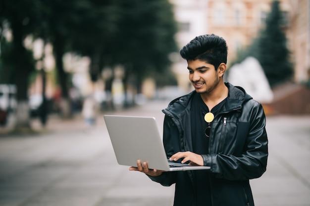 Giovane uomo indiano che sta all'aperto con il computer portatile nella parte anteriore