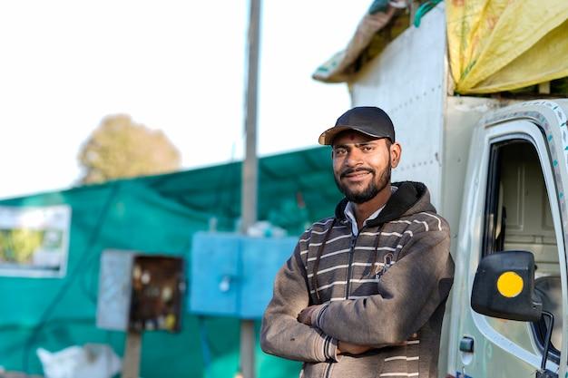 自分の輸送車両で立っている若いインド人