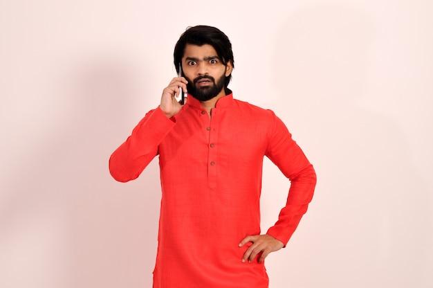 스마트폰으로 말하는 젊은 인도 남성은 놀라움과 놀란 표정으로 충격을 받았습니다.