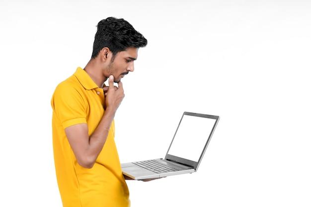 흰색 바탕에 노트북을 사용하는 젊은 인도 남자.