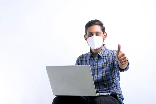 Young indian man using laptop over white background.