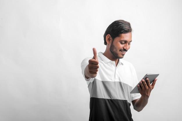 흰색 배경 위에 태블릿을 사용하는 젊은 인도 남자.