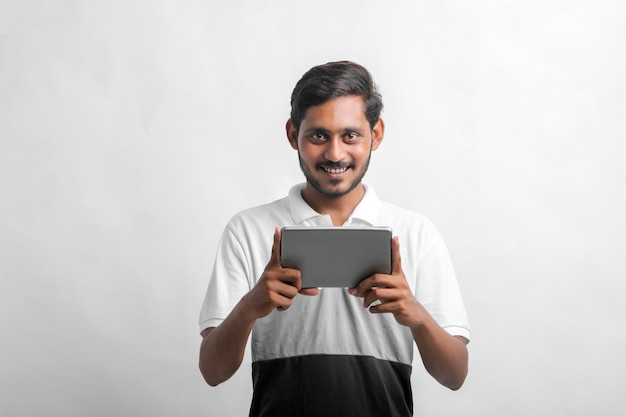 Young indian man using tablet over white background.