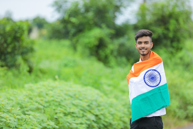 Young indian man waving indian national flag over nature background