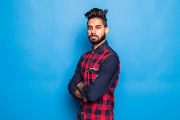 孤立した青い空間にカジュアルな立っている身に着けている若いインド人