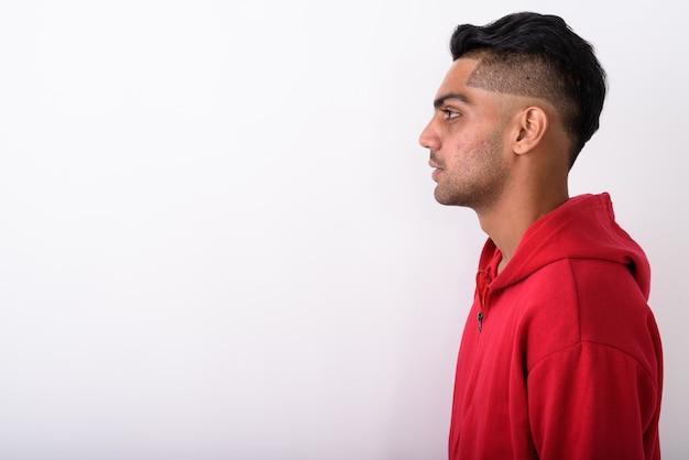 Молодой индийский мужчина в толстовке с капюшоном на белом