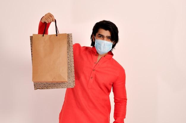 쿠르타와 마스크를 쓰고 쇼핑백을 보여주는 인도 청년 covid19