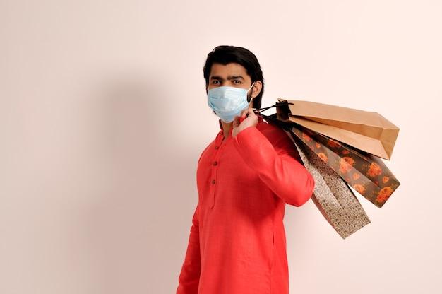 쇼핑백 마스크와 함께 쿠르타를 입은 젊은 인도 남성 코비드1