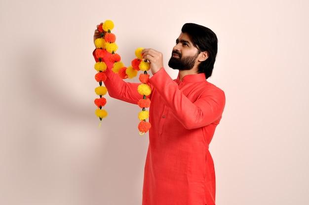 금잔화 꽃 화환 측면 보기를 들고 오렌지 kurta를 입고 젊은 인도 남자