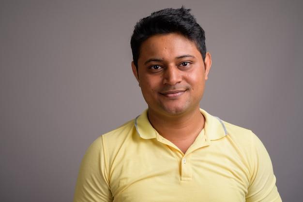 Young indian man wearing yellow polo shirt