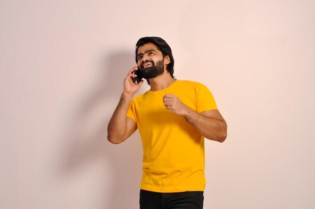 노란색 티셔츠를 입은 젊은 인도 남자 휴대 전화로 이야기하고 위를 올려다보며 웃고
